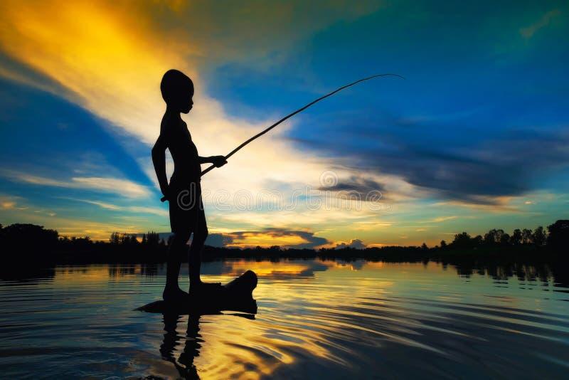 Рыбная ловля силуэта на заходе солнца стоковые изображения rf