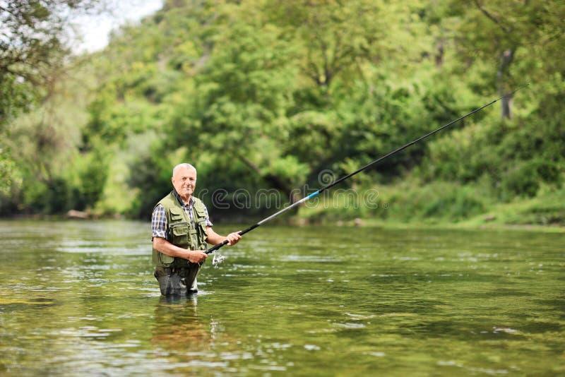 Рыбная ловля старшего человека в реке на солнечный день стоковые фотографии rf