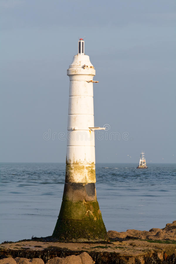 Рыбная ловля траулера в море около малого белого маяка стоковые фотографии rf