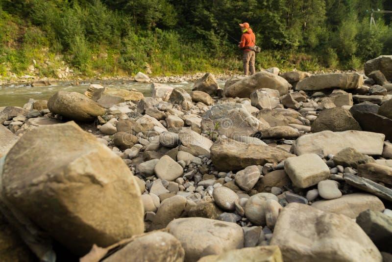 Рыбная ловля форели в реке горы стоковое фото