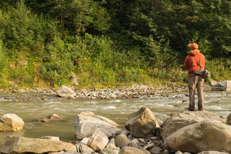 Рыбная ловля форели в реке горы стоковое изображение