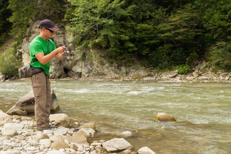 Рыбная ловля форели в реке горы стоковые фотографии rf