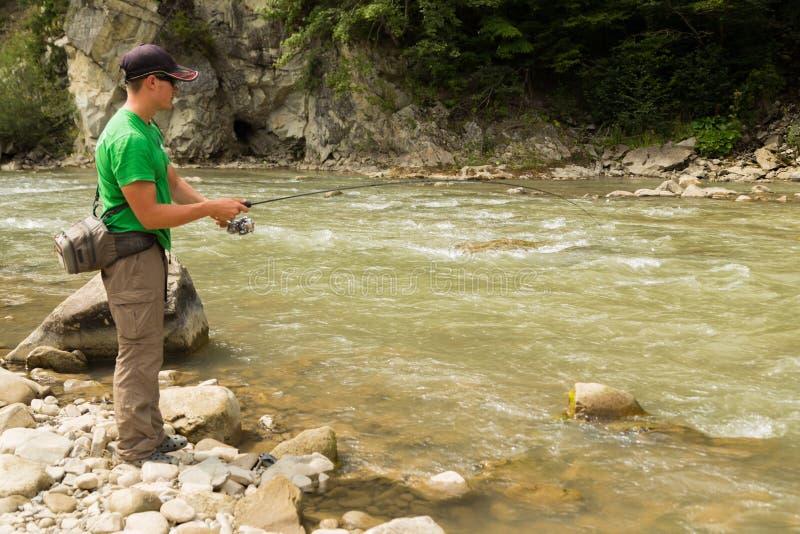 Рыбная ловля форели в реке горы стоковые изображения rf