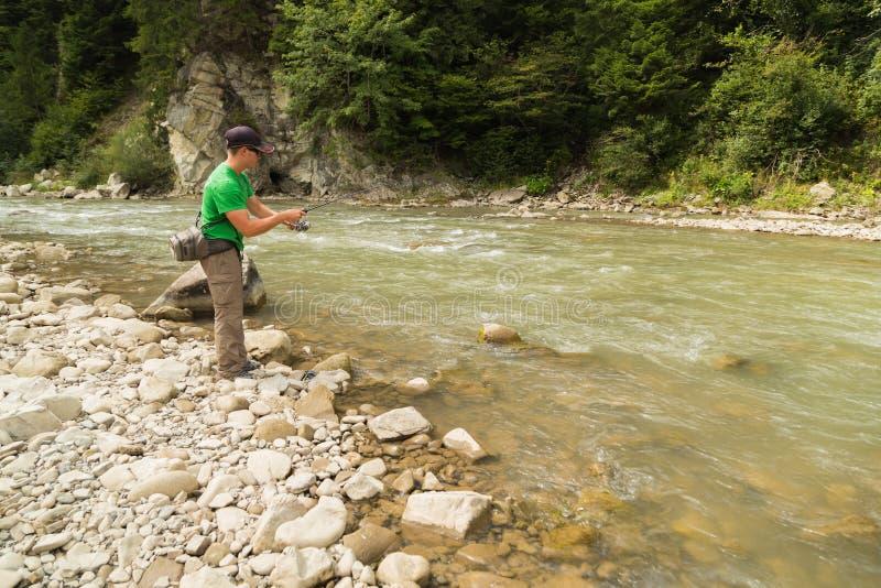 Рыбная ловля форели в реке горы стоковая фотография