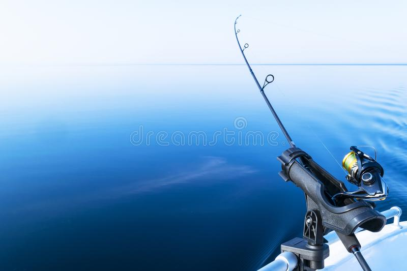 Рыболовная удочка закручивая с линией концом-вверх Рыболовная удочка в держателе штанги в рыбацкой лодке должной день рыбозавода  стоковое изображение rf