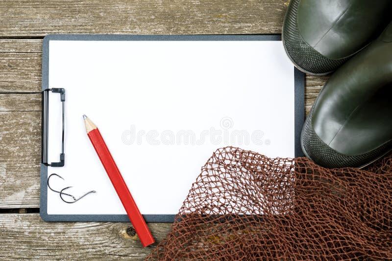 Рыболовные принадлежности - рыбная ловля, карандаш, крюки, ботинки, деревянная предпосылка стоковое изображение rf