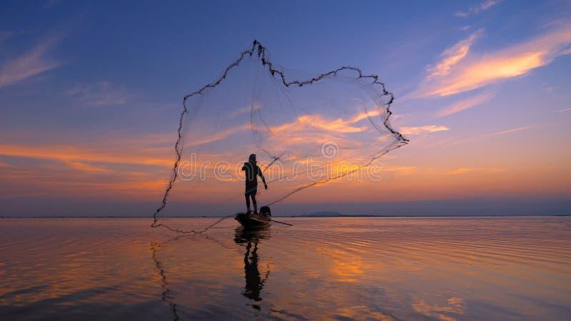 Рыболовные сети рыболова силуэта на шлюпке Силуэт рыболовов используя рыб похожей на курятник ловушки улавливая в озере с красивы стоковое фото rf