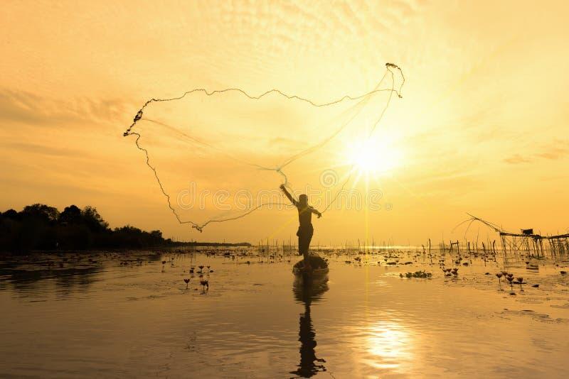 Рыболовные сети рыболова силуэта на шлюпке Таиланд, силуэт рыболовов используя сети для того чтобы уловить рыб на озере в morni стоковые изображения rf