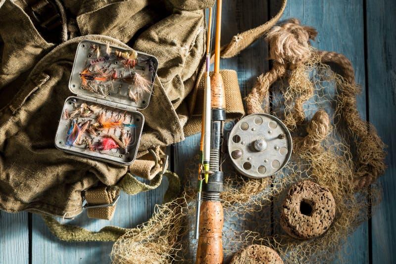 Рыболовные снасти с мухами и штангами рыбной ловли на деревянном столе стоковое фото rf