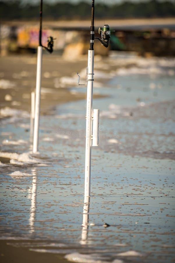Рыболовные удочки выкопали в побережье пляжа океана стоковые изображения rf