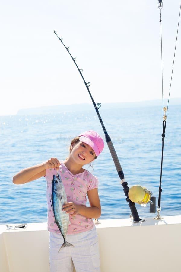 Рыболовство маленькой девочки ребенка в шлюпке держа маленьких тунцов удит catc стоковое фото