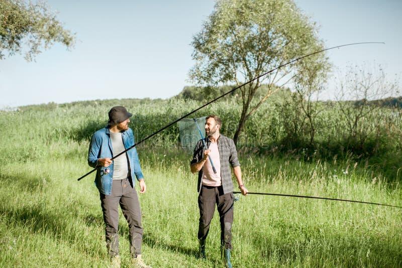 Рыболовы идя на зеленую лужайку стоковые изображения rf