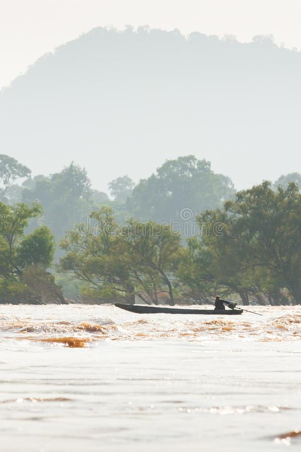 Рыболовы Лаоса на рыбацкой лодке в речных порогах Меконга Меконг идя переполнение Тропические лес и горы стоковые изображения
