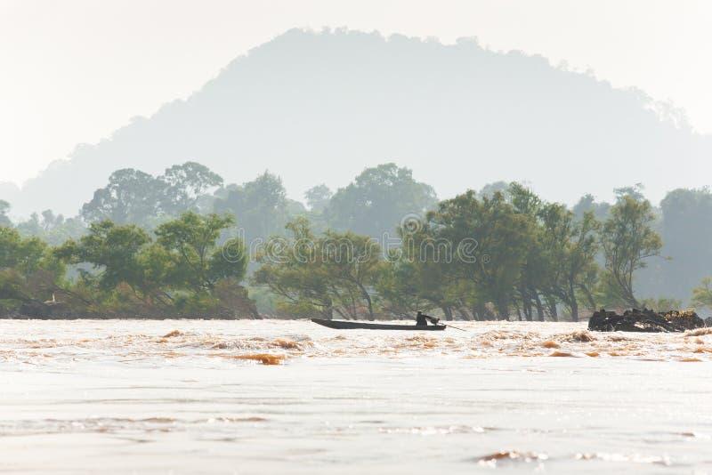 Рыболовы Лаоса на рыбацкой лодке в речных порогах Меконга Меконг идя переполнение Тропические лес и горы стоковое фото