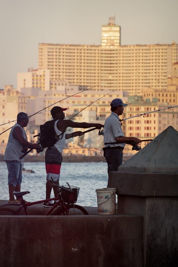 Рыболовы на зоре на известной морской дамбе Malecon в Гаване стоковые изображения