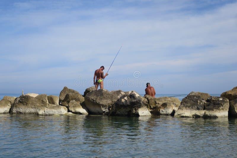 Рыболовы на утесах которые удят в море стоковое фото rf