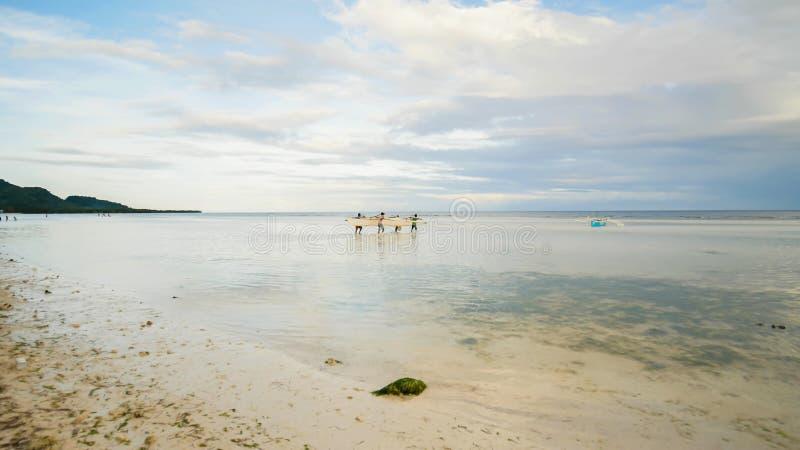 Рыболовы носят шлюпку к морю Остров Bohol philippines стоковое фото