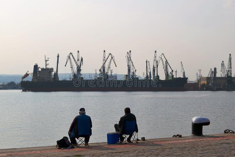 Рыболовы удя со штангой на пристани в морском порте на теплый windless день осени стоковое изображение rf