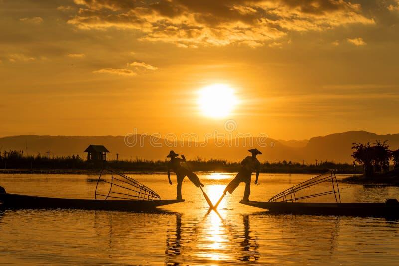 Рыболовы Inle знать для практиковать отличительный стиль rowing который включает стоять на кормке на одной ноге и оборачивать th стоковая фотография