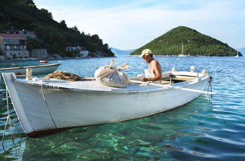 Рыболов в деревянной шлюпке, Mljet, Хорватии. стоковые фотографии rf