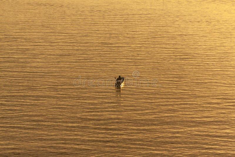 Рыболов в шлюпке на спокойной воде во время восхода солнца в Таиланде стоковые изображения rf