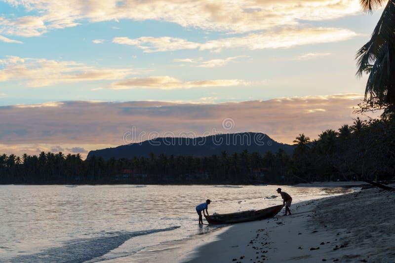 Рыболов 2 идет к морю в шлюпке на зоре стоковое фото