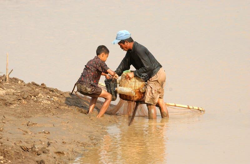 Рыболов ищет рыб в dawuhan резервуаре в Madiun стоковые фото