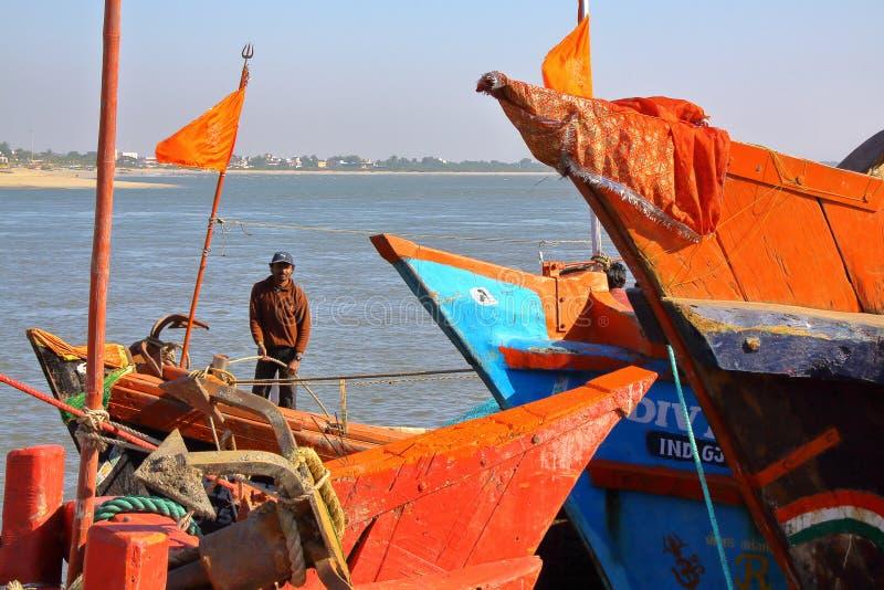 Рыболов и красочные деревянные шлюпки на рыбном порте в острове Diu стоковые фотографии rf