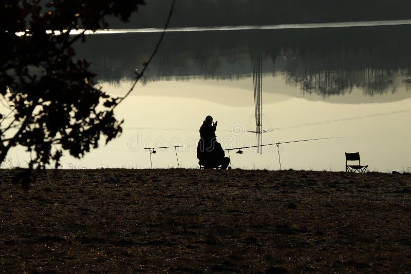 Рыболов курит сигарету и разговаривать с его другом пока он ждет рыб Запруда около Frydek-Mistek в чехии на восходе солнца стоковое изображение rf