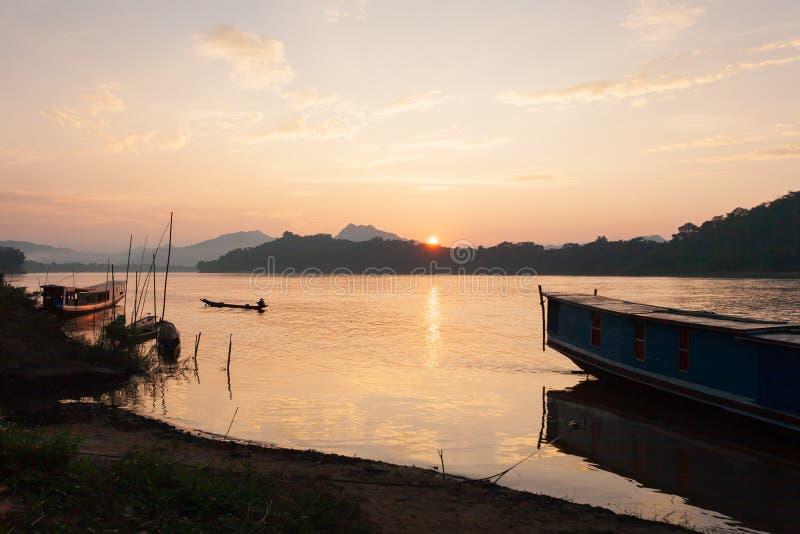 Рыболов Лаоса с удить деревянную шлюпку в Меконге на заходе солнца жизнь просто Традиционные передние планы шлюпки Лаоса красивей стоковые изображения