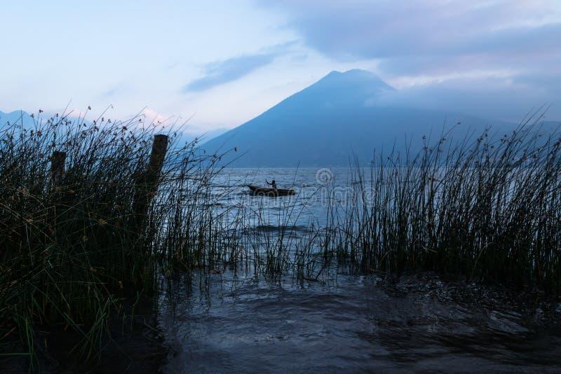 Рыболов между травой во время захода солнца на озере Atitlan на береге San Marcos, Гватемалы стоковые изображения