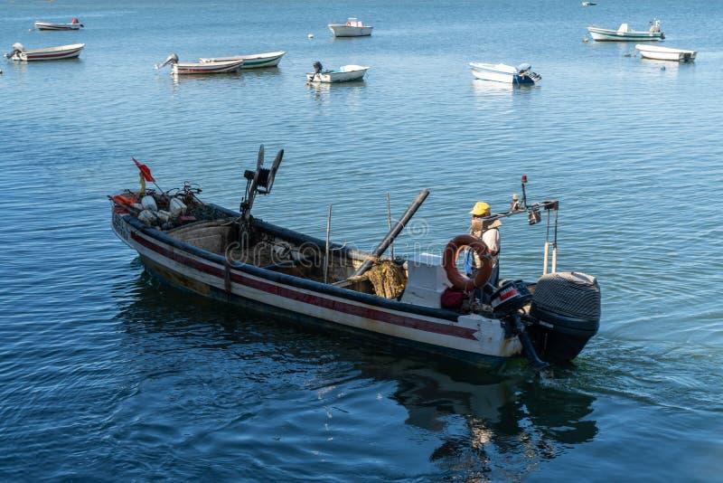 Рыболов на его шлюпке во время рабочего дня стоковое изображение rf