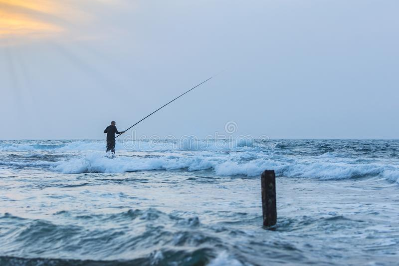 Рыболов на заходе солнца в волнистых водах стоковая фотография rf