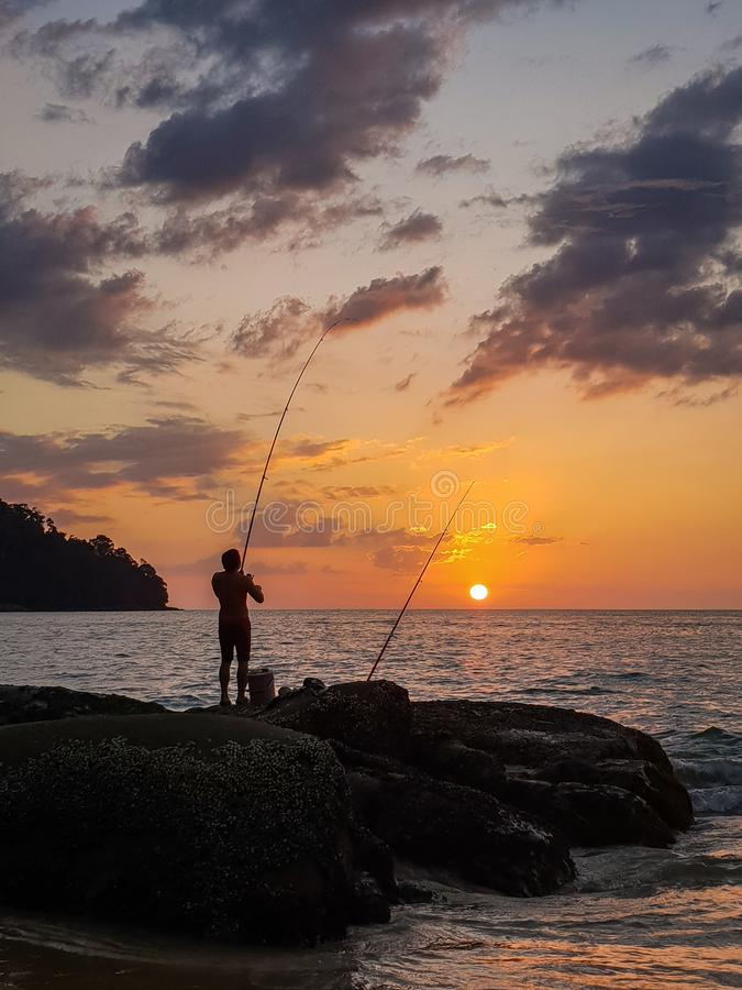 Рыболов на заходе солнца, Таиланд стоковая фотография rf