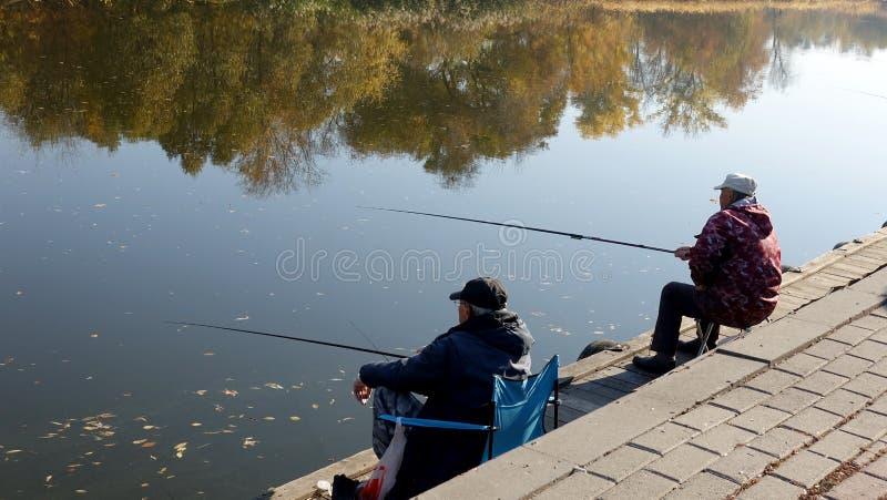 Рыболов 2 на речном береге с рыболовными удочками стоковое изображение rf