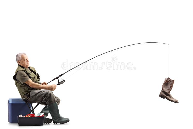 Рыболов на стуле со старым ботинком на рыболовной удочке стоковые изображения