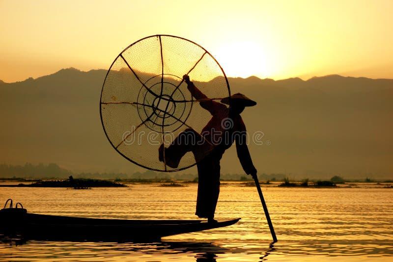 Рыболов представляет на восходе солнца, озере Inle, Мьянме стоковые изображения