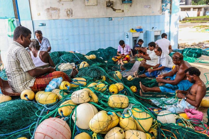 Рыболов работая на рыболовных сетях в гавани Mirissa, Шри-Ланке стоковые фотографии rf