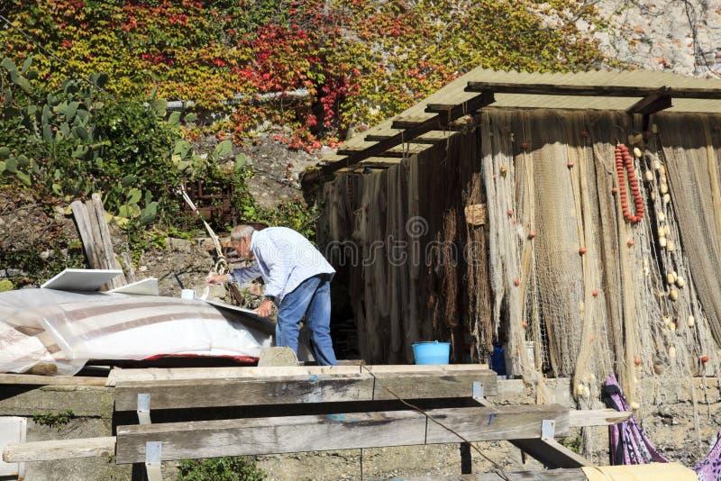 Рыболов работая около залива Сан Fruttuoso, Genova, Лигурии, Италии, Европы стоковое фото