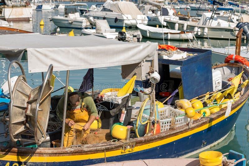 Рыболов ремонтирует рыболовные сети на рыбацкой лодке стоковое фото