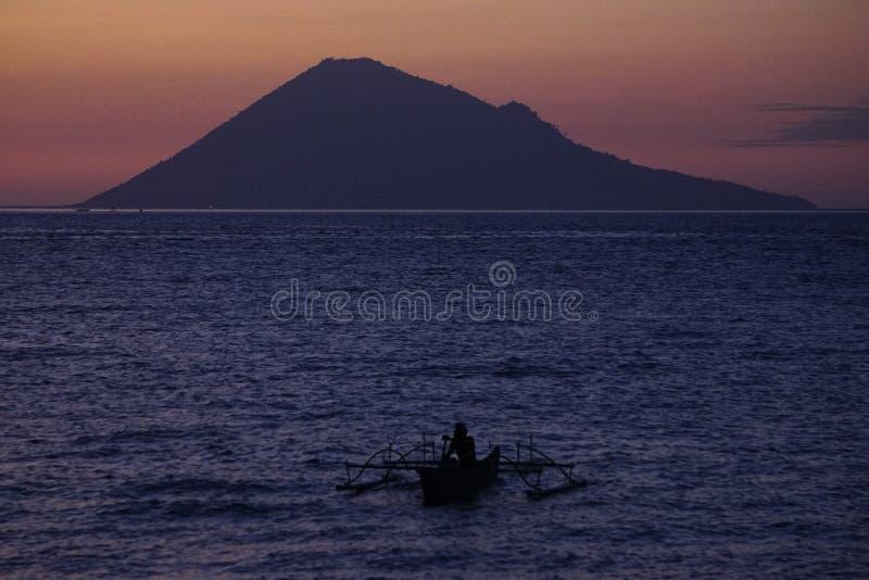 Рыболов самостоятельно с предпосылкой острова Manado Tua стоковое изображение