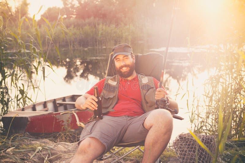 рыболов сидя с рыболовной удочкой и пивом, наслаждается, отдых и хобби стоковое изображение rf