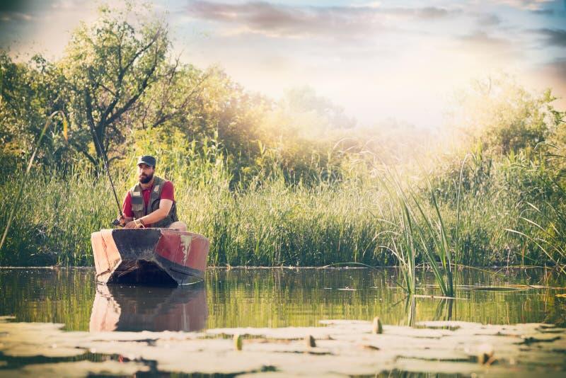 Рыболов с рыболовными удочками удит в деревянной шлюпке против предпосылки красивых природы и озера или реки стоковое изображение