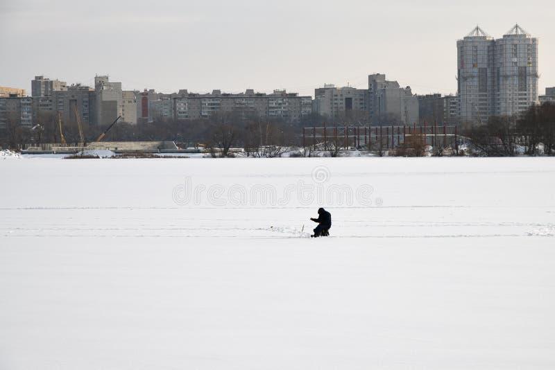 рыболов удит зиму льда отверстия рыболовства стоковое фото