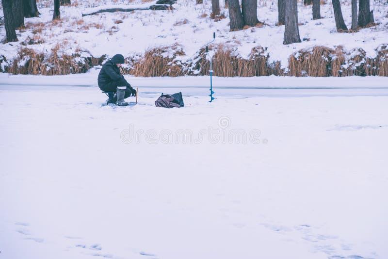 Рыболов улавливает рыбу на рыбной ловле зимы стоковая фотография