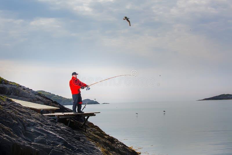 Рыболов человека удит от берега В закручивая руках стоковое изображение rf