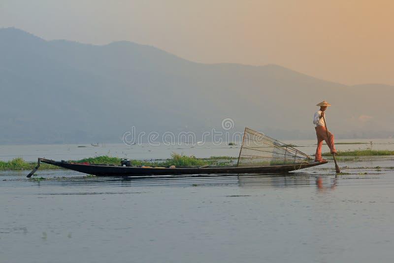 Рыболов Inle используя ноги гребли стоковое фото