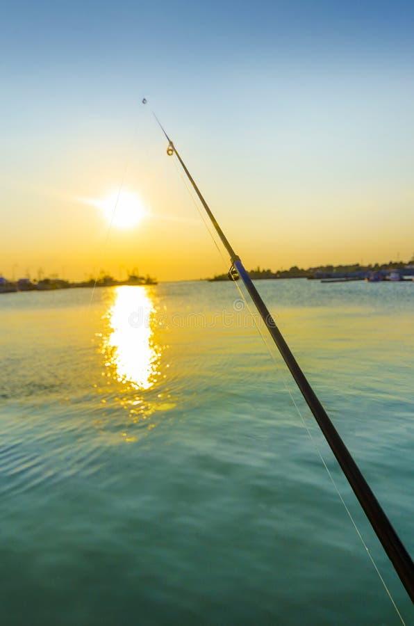 Рыболовная удочка в океане на зоре стоковая фотография rf