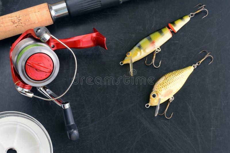 Рыболовные снасти - закручивать рыбной ловли, удя линия, крюки и Wobblers на предпосылке стоковые изображения