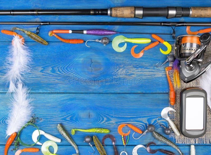 Рыболовные снасти - закручивать рыбной ловли, удя линия, крюки, навигатор и вьюрок на голубой деревянной предпосылке стоковая фотография